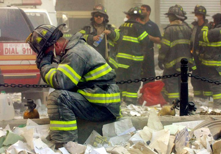 A firefighter bows in grief after the World Trade Center buildings collapsed on Sept. 11, 2001.