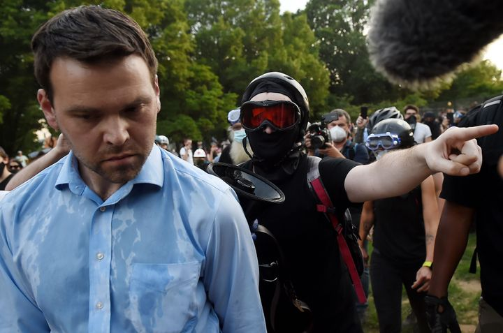 Far-right pro-Trump propagandist and One America News correspondent Jack Posobiec is escorted out of Lincoln Park by anti-rac