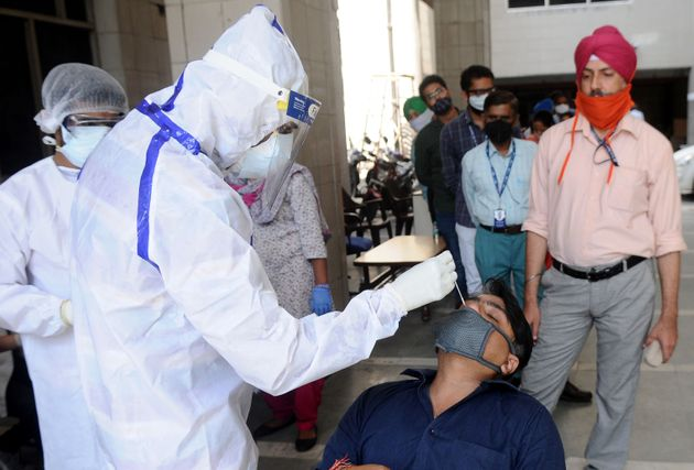 PATIALA, INDIA - SEPTEMBER 11: Health workers wearing PPE kit conduct COVID-19 Rapid Antigen test of...