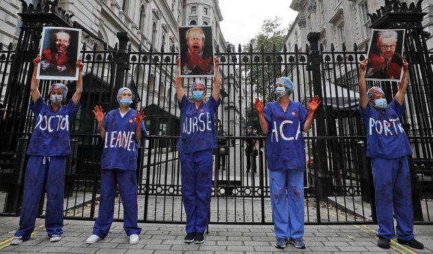 Nurses stand in front of the entrance to Downing Street as they take part in a demonstration of NHS workers at hospitals across London to demand a 15 per cent pay rise by the government in London, Wednesday, Aug. 26, 2020.(AP Photo/Kirsty Wigglesworth)