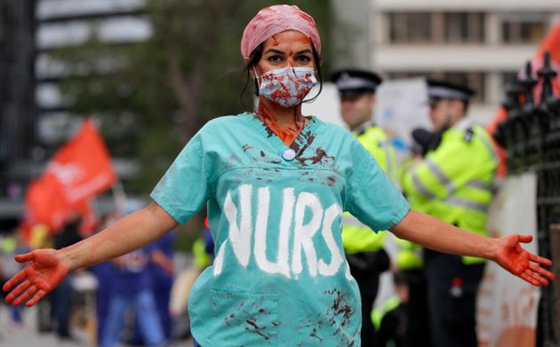 A nurse covered in fake blood takes part in a demonstration of NHS workers at hospitals across London...