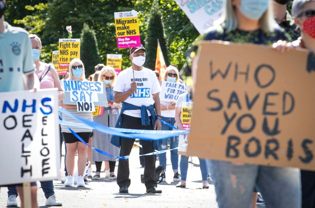 National Health Service (NHS) workers pose with placards, during a socially distanced demonstration as...