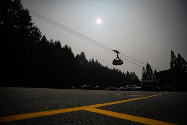 Smoke from wildfires burning in the U.S. obscures the sun as the Grouse Mountain tram transports people...