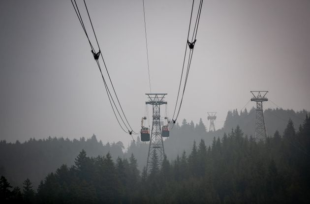 Smoke from wildfires burning in the U.S. fills the air as Grouse Mountain trams transport people up and...