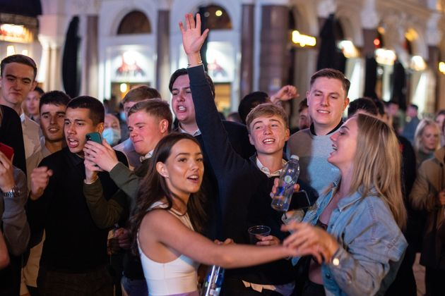 People sing and dance as they watch a street performer in Leicester Square, in London's West End before...