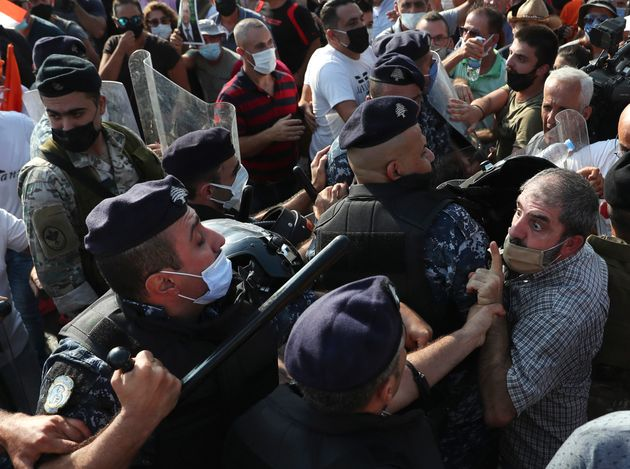 A supporter of Lebanese President Michel Aoun argues with riot police as they try to take a main road...