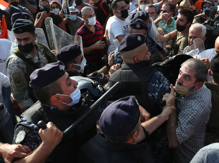 A supporter of Lebanese President Michel Aoun argues with riot police as they try to take a main road that links to the presi