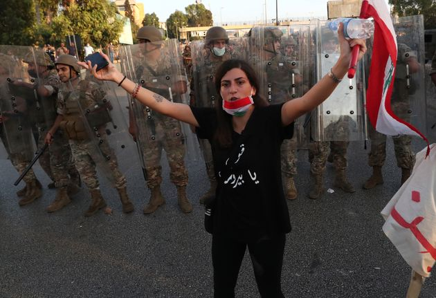 An anti-government protester tries to calm down other protesters, as she stands in front of Lebanese...
