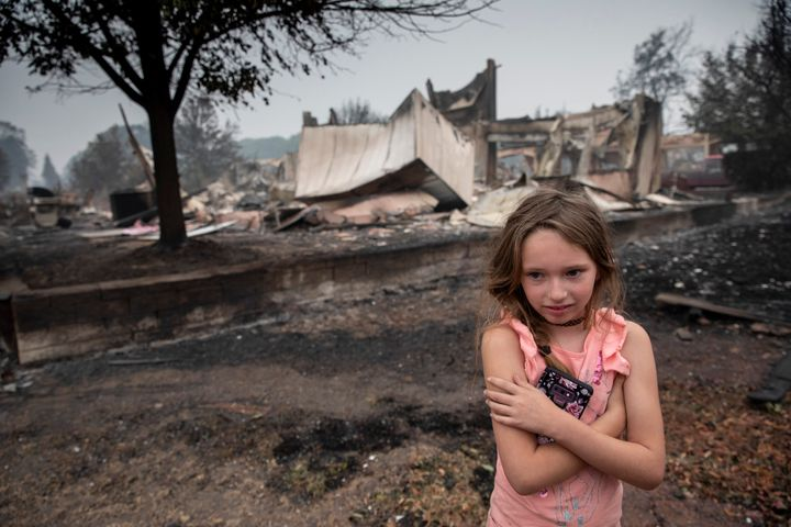 Ellie Owens, 8, from Grants Pass, Ore., looks at fire damage Friday, Sept. 11, 2020, as destructive wildfires devastate the r