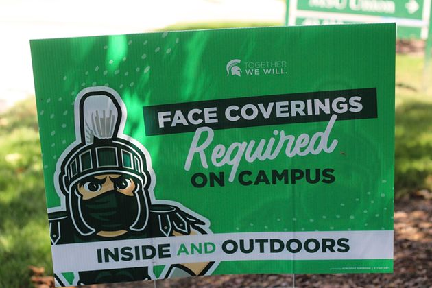 A sign outside the Michigan State University Student Union building alerts students to MSU's face covering...