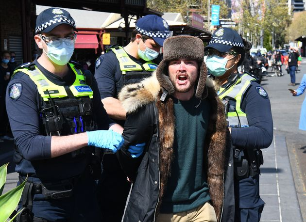 Police detain an anti-lockdown protester at Melbourne's Queen Victoria