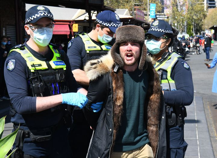Police detain an anti-lockdown protester at Melbourne's Queen Victoria Market.