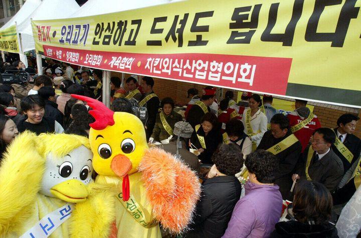 """""""닭고기, 오리고기, 안심하고 드셔도 됩니다."""" 조류독감이 돌면 사람들이 닭고기를 꺼리기 때문에 영세한 치킨집들이 타격을 받는다. 2004년에 서울 명동에서 닭고기 먹기 캠페인을 벌이는 모습이다. 이정용 기자가 찍었다."""
