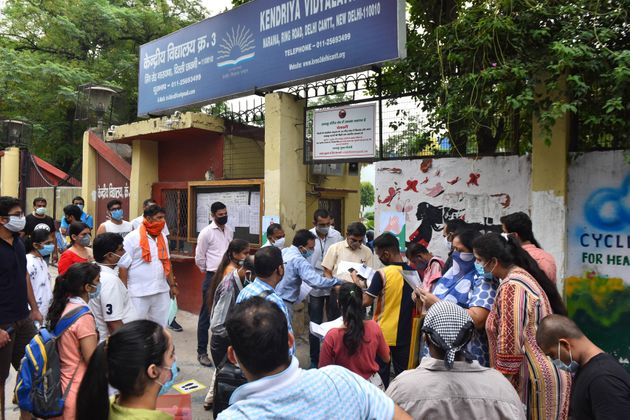 NEET aspirants and parents wait outside the examination centre at Naraina, on September 13, 2020 in New