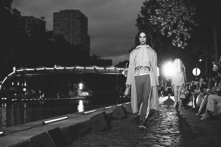 Ενα μοντέλο βηματίζει στην αυτοσχέδια πασαρέλα που στήθηκε στις όχθες του Καναλιού του St. Martin στο Παρίσι κατά την διάρκεια της επίδειξης μόδας του οίκου Courreges για την Ανοιξη και το Καλοκαίρι του 2020.