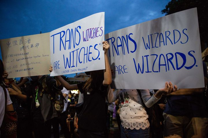Anti-government protesters in Bangkok hold signs calling out J.K. Rowling's transphobic Twitter comments as they take part in a Harry Potter themed rally in front of Democracy Monument on Aug. 3.