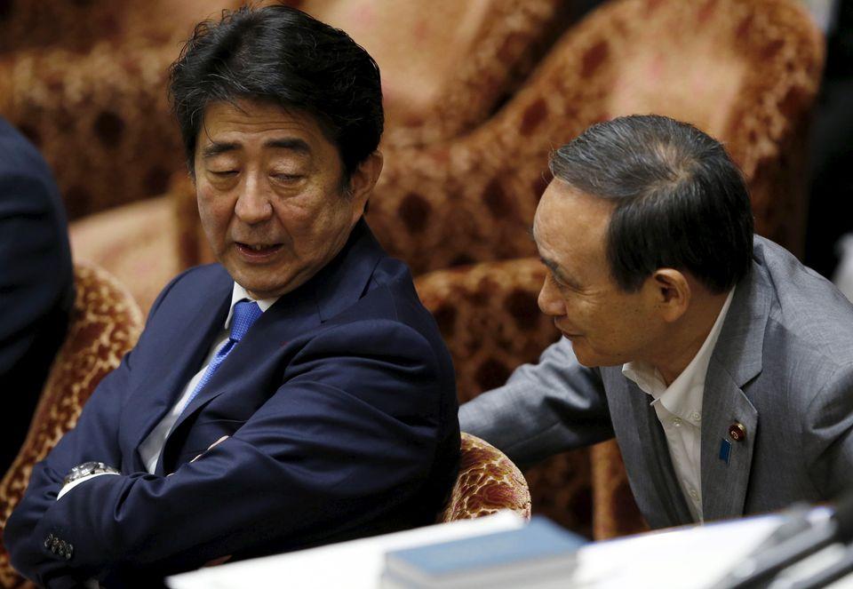 (자료사진) 중의원(하원) 회의에 참석한 아베 신조 일본 총리가 스가 요시히데 관방장관과 대화를 나누고 있다. 도쿄, 일본. 2015년