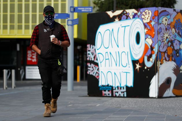 A man wearing a mask walks past street art in Prahran on September 14, 2020 in Melbourne,