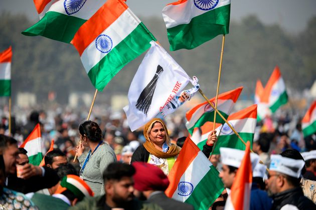 Supporters of the Aam Aadmi Party (AAP) hold party flags and Indian national flags before Arvind Kejriwal...