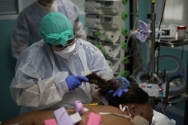 Una sanitaria peina a una enferma de Covid-19, en un hospital de Marsella,
