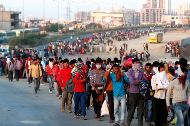 Migrant workers walk towards a bus station along a highway with their families as they return to their...