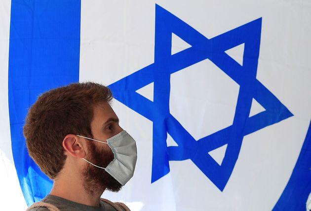 Un joven pasa ante una bandera de Israel en el centro de Jerusalén, el pasado