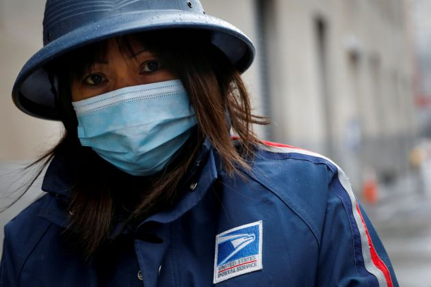 A USPS employee works in the rain in Manhattan during the outbreak of the coronavirus in New York City...