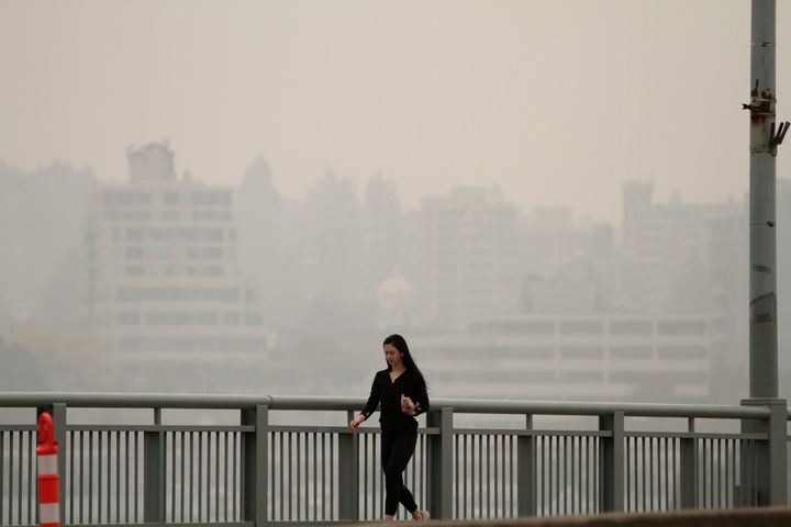 A woman walks on Granville Bridge as smoke from wildfires fills the air in Vancouver, B.C. on Sept. 12, 2020.