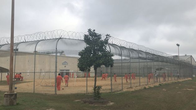Detained immigrants play soccer behind a barbed wire fence at the Irwin County Detention Center in Ocilla,...