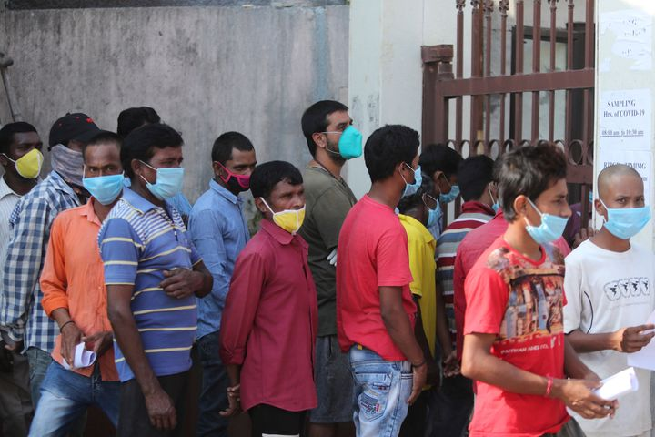 People wait in line to receive COVID-19 tests at a government hospital in Jammu, India on Tuesday.