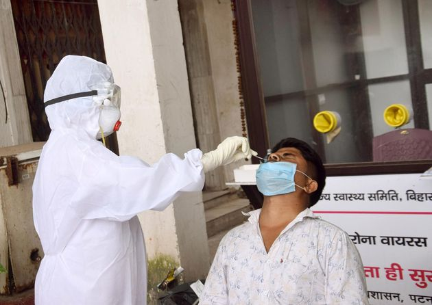 A health worker collects a swab sample from a man for coronavirus testing, at Gardiner Hospital, on August...