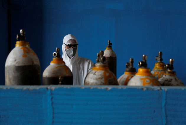 A medical worker stands next to an oxygen cylinder at the Yatharth Hospital in Noida, on the outskirts...
