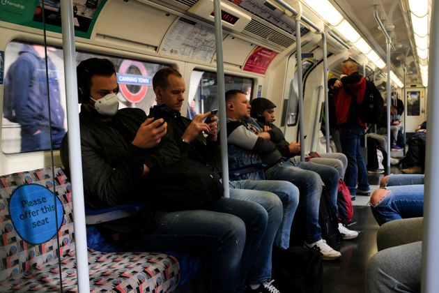 Commuters, some wearing protective masks to protect against coronavirus travel on a Jubilee Line underground...