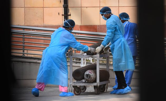 Medical workers draw a cart with oxygen cylinders outside the Covid-19 ward, at Lok Nayak Jai Prakash...