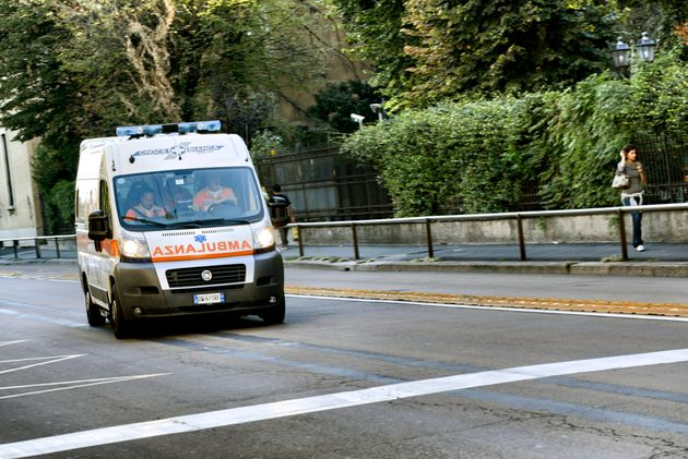 Milan, Italy - September 14, 2012: An ambulance with three paramedics is running fast in Milan city centre...