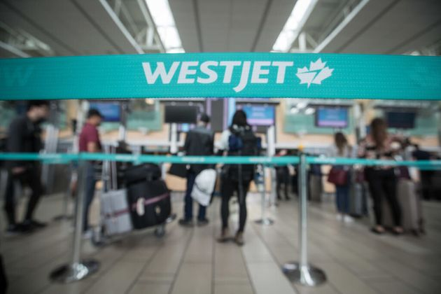 Travellers stand in line at Vancouver International Airport in May 2019. WestJet was previously offering...