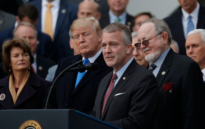 Sen. Sullivan, foreground, speaks at a ceremony celebrating Donald Trump's tax cuts. His fortunes could depend on whether Alaskans distinguish him from the president.