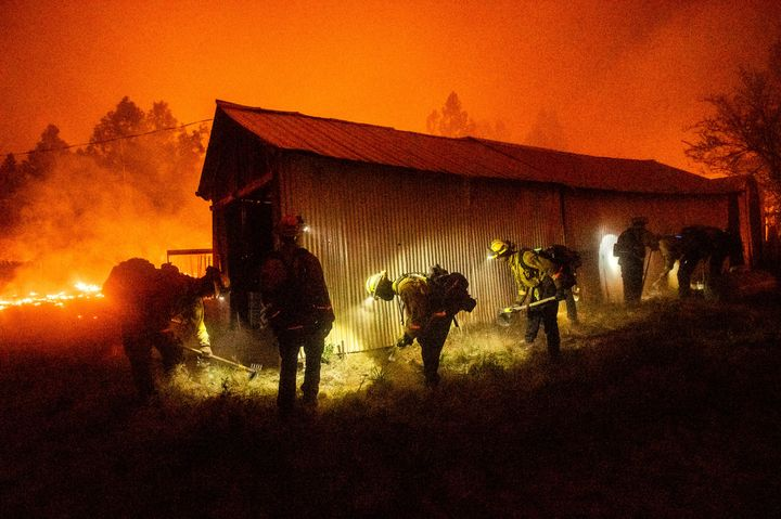 A hand crew clears vegetation from around a barn as the Bear Fire burns through the Berry Creek area of Butte County, Calif.,