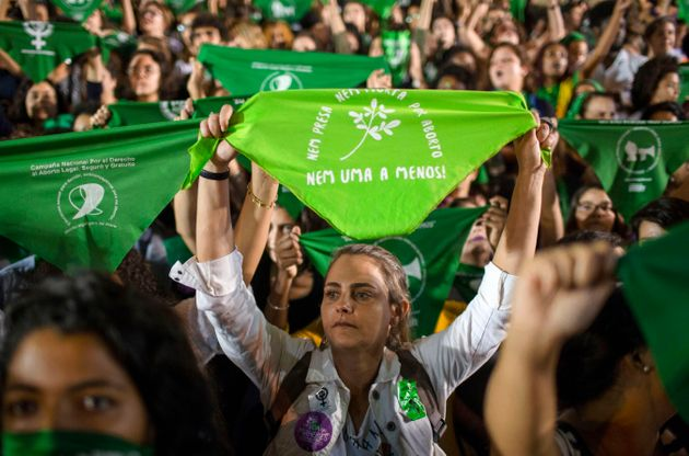 Mulheres erguem lenços da cor verde, símbolo da luta pela discriminalização...