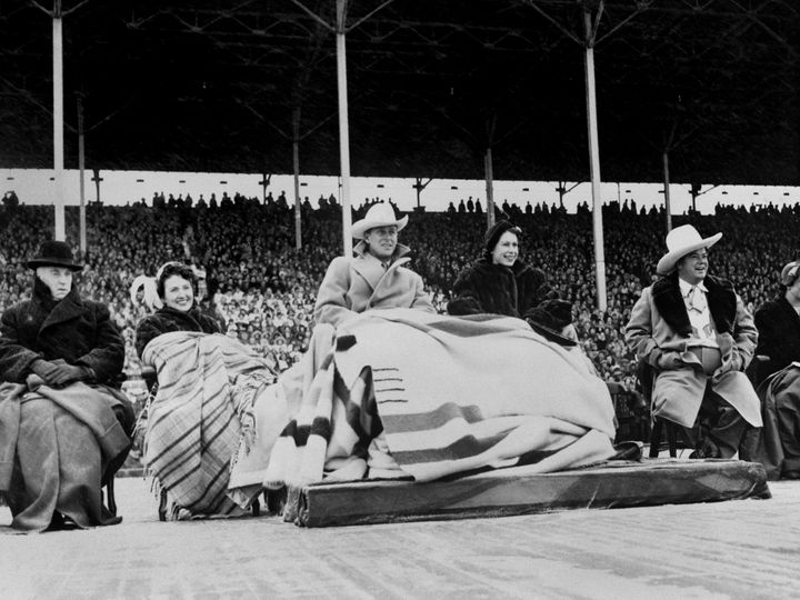 Princess Elizabeth and the Duke of Edinburgh wearing a blanket (a wedding present from Canada) watching the the Calgary Stampede during their 1951 visit.