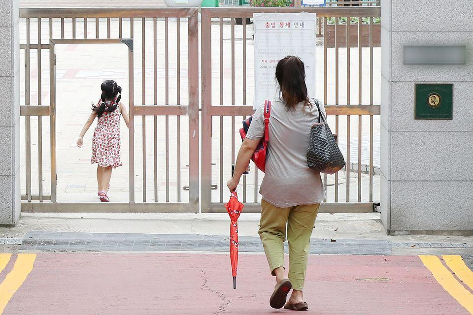 9월 16일 서울의 한 초등학교에서 학부모가 자녀를 오후 돌봄교실에 바래다주고