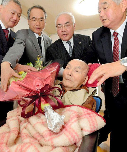 弁護団から花束を贈られた宮田浩喜さん(中央)=2019年3月28日午後0時35分ごろ、熊本市西区、代表撮影
