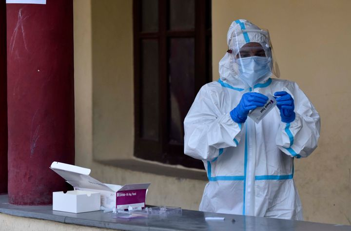 A health worker works with a rapid antigen based Covid-19 test kit at Drya Ganj on July 27, 2020 in New Delhi