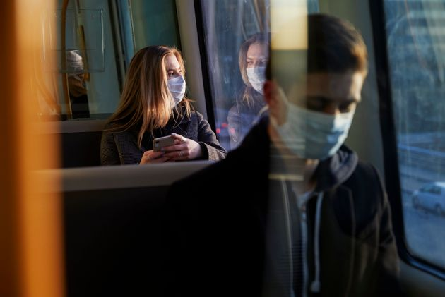 young woman sitting in train wearing protective mask, using