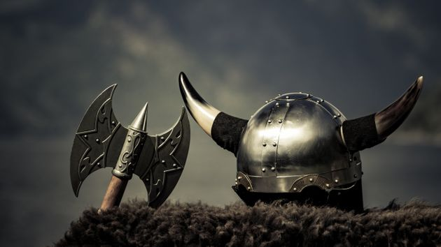 Viking helmet with axe on fjord shore in Norway. Tourism and traveling
