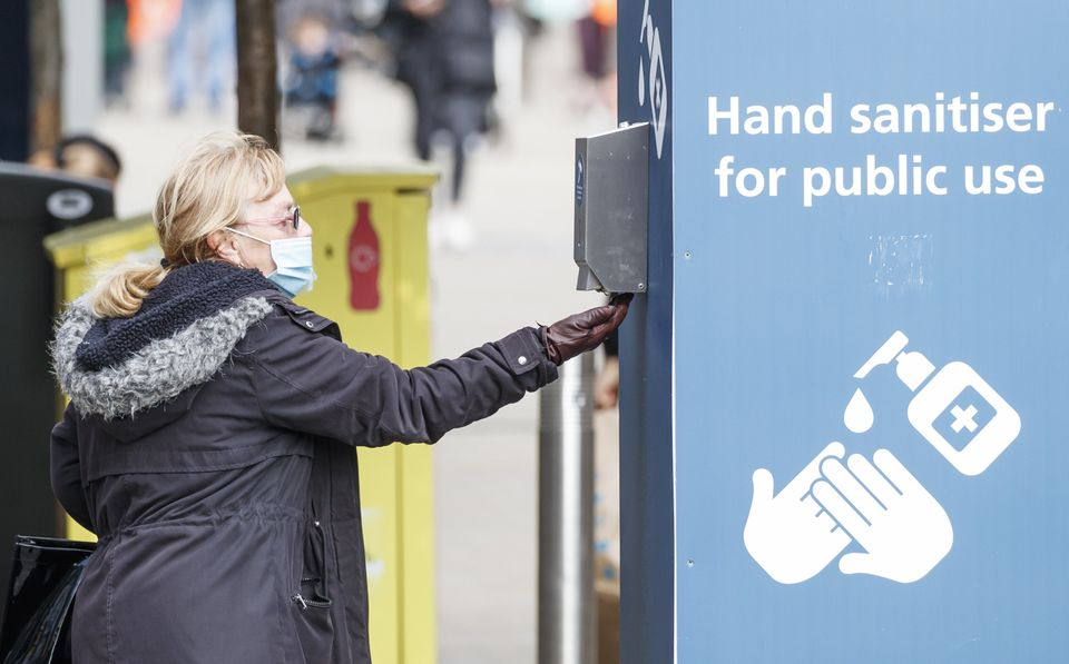 A woman uses a public hand sanitiser in Leeds city centre.