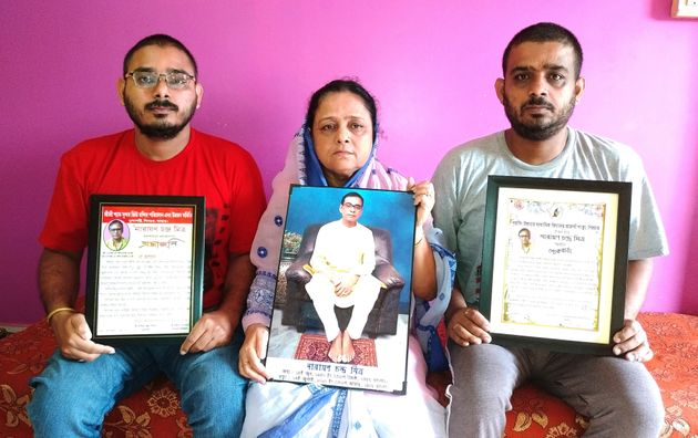 Anindita Mitra, 61, flanked by her sons Satyajit Mitra, right and Abhijit Mitra, pose with portraits...