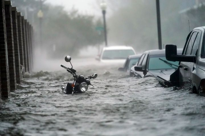 Cars and a motorcycle are underwater as water floods a street, Wednesday in Pensacola, Fla.