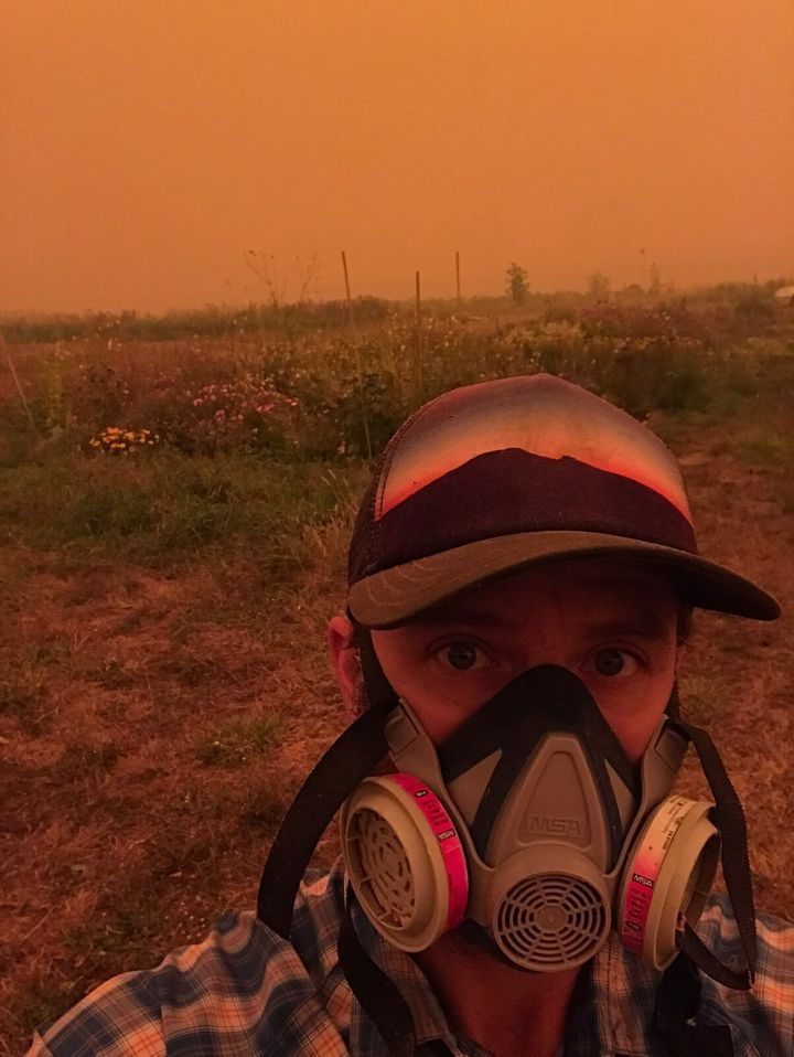 """Farmer Conner Voss wears a mask at <a href=""""https://digginrootsfarm.com/"""" role=""""link"""" data-ylk=""""subsec:paragraph;itc:0;cpos:__RAPID_INDEX__;pos:__RAPID_SUBINDEX__;elm:context_link"""">Diggin' Roots Farm</a> in Oregon's Willamette Valley."""