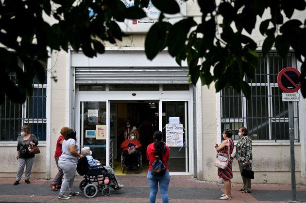 La gente hace cola en la puerta de un centro de salud del barrio de Vallecas